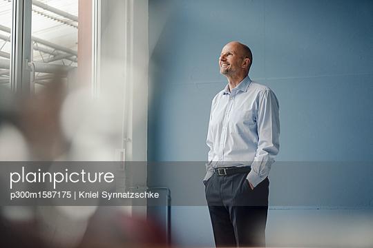 Smiling mature businessman looking out of window - p300m1587175 von Kniel Synnatzschke