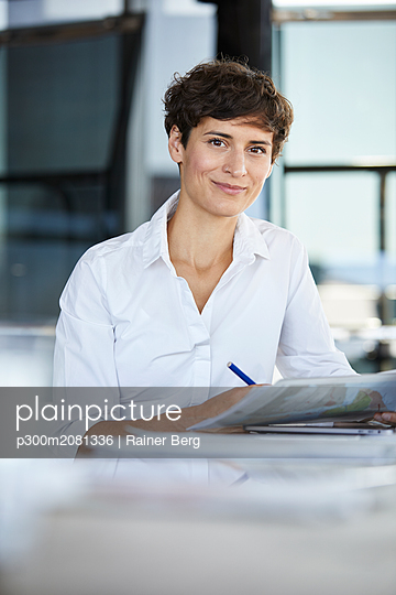 Portrait of confident businesswoman sitting at desk in office with laptop and document - p300m2081336 by Rainer Berg
