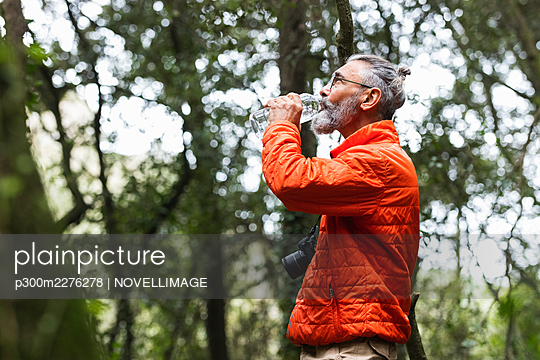 Senior man with camera drinking water while standing in forest - p300m2276278 by NOVELLIMAGE