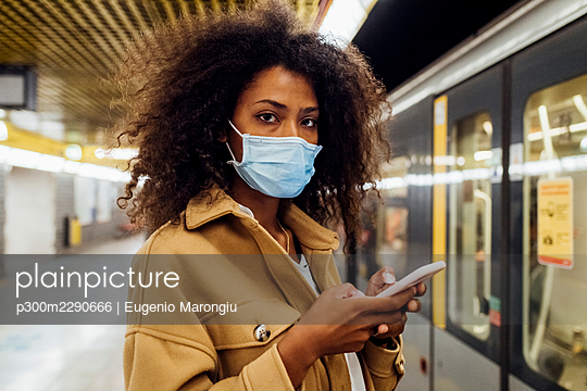 Young woman with protective face mask holding mobile phone while standing in subway - p300m2290666 by Eugenio Marongiu
