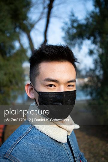 Portrait of Asian man with community mask - p817m2179112 by Daniel K Schweitzer