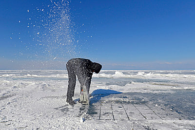 Russia, Lake Baikal, man opening an ice hole with a motor saw for ice diving - p300m1053811 by Gerald Nowak
