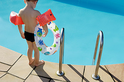 Back view of little boy with floating tire and water wings standing at pool edge - p300m1115018f by Guntmar Fritz