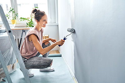 Young woman painting wall with paint roller while crouching at home - p300m2225088 by Bartek Szewczyk