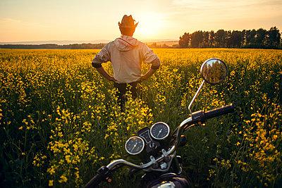 Mari man standing near motorcycle in field of flowers - p555m1420950 by Aliyev Alexei Sergeevich
