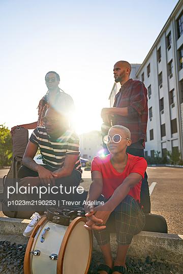 Portrait confident musicians in sunny parking lot - p1023m2190253 by Trevor Adeline