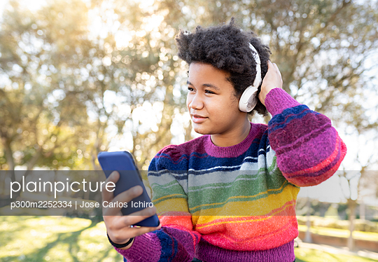 Girl wearing headphones using mobile phone while sitting with hand in hair at park - p300m2252334 by Jose Carlos Ichiro