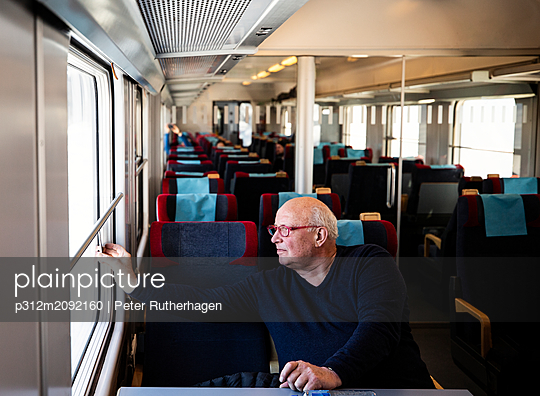 Senior man looking through train window - p312m2092160 by Peter Rutherhagen