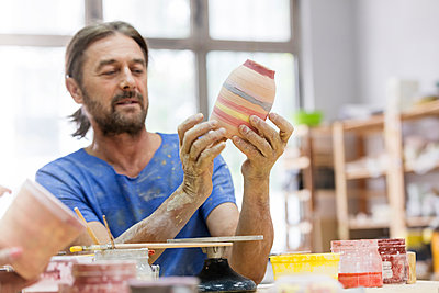 Mature man painting pottery vase in studio - p1023m1173730 by Rafal Rodzoch