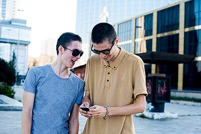 Caucasian men using cell phone in city - p555m1420561 by Aleksander Rubtsov