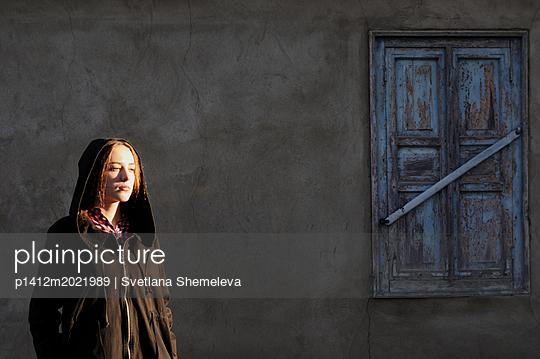Frau vor einem Fenster mit geschlossenen Fensterläden - p1412m2021989 von Svetlana Shemeleva