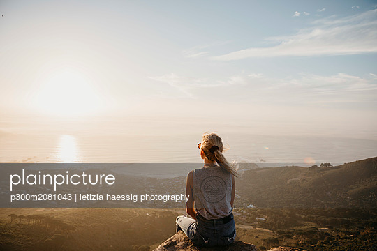 South Africa, Cape Town, Kloof Nek, woman sitting on rock at sunset - p300m2081043 by letizia haessig photography