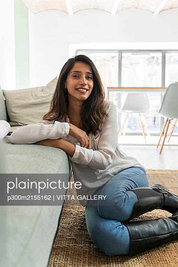 Young indian woman sitting on the floor, looking at camera - p300m2155162 von VITTA GALLERY