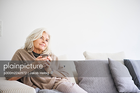 Thoughtful retired woman holding coffee cup while sitting on sofa against white wall at apartment - p300m2242972 by Jakob Helbig