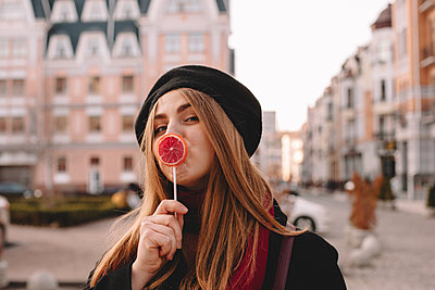 Young woman kissing lollipop while standing on city street - p1166m2106666 by Cavan Images