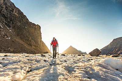 Back lit mountaineer crosses glacier on Baffin Island. - p1166m2205811 by Cavan Images