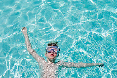 Child with goggles floating in pool. - p1262m1444777 by Maryanne Gobble