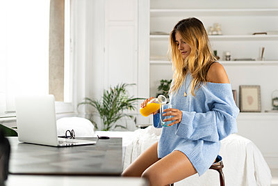 Young woman sitting in bedroom at home pouring orange juice into a glass - p300m2058829 by Eloisa Ramos