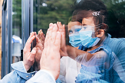 Family with protective face masks greeting through glass door during COVID-19 - p300m2293290 by Angel Santana Garcia