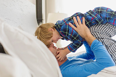 Father being playful with young son in bed. - p328m840984f by Hero Images