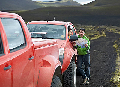 Couple reading map by customised SUV;  Hekla;  Fjallabak;  Iceland - p429m860233f by Henn Photography