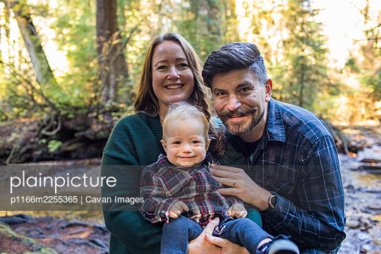 Mother and father holding their son outdoors in nature. - p1166m2255365 by Cavan Images