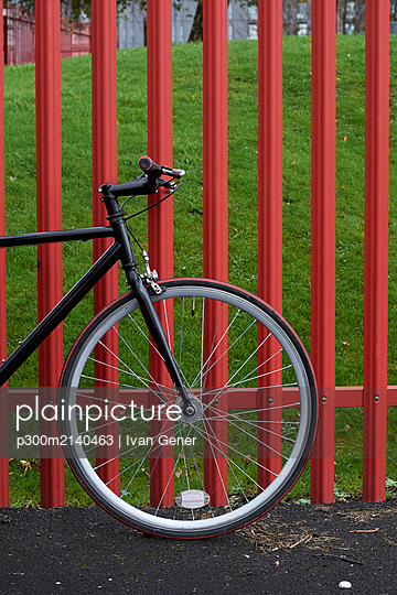 Bicycle parked on road by fence in park - p300m2140463 by Ivan Gener