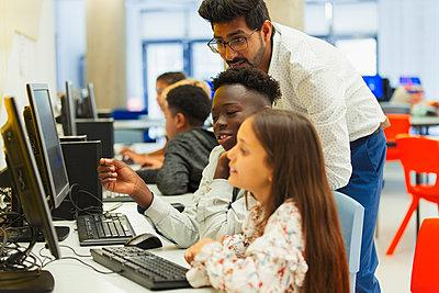 Teacher helping junior high students using computer in computer lab - p1023m2067140 by Paul Bradbury