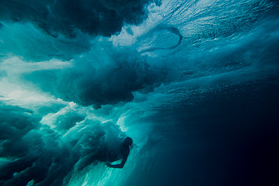 Underwater view of a surfer being wiped out by a powerful wave - p1166m2096679 by Cavan Images