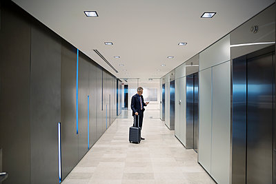 Businessman with luggage waiting for elevator in airport corridor - p1192m1183769 by Hero Images
