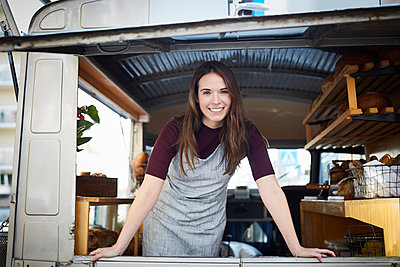Portrait of smiling young female owner standing in food truck - p426m1536953 by Maskot
