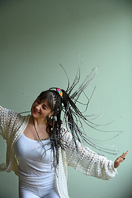 Young woman with dreadlocks dancing - p427m2203634 by Ralf Mohr