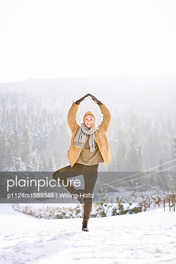 Young woman balancing on one leg in snowy landscape - p1124m1589348 by Willing-Holtz
