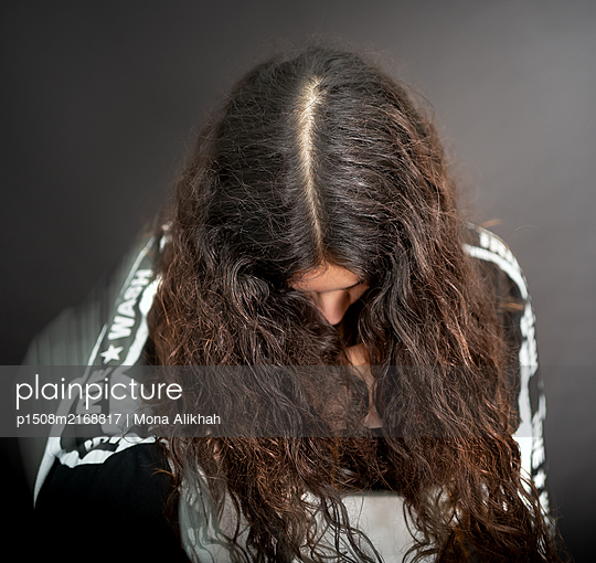 Young woman with long hair looking down - p1508m2168817 by Mona Alikhah