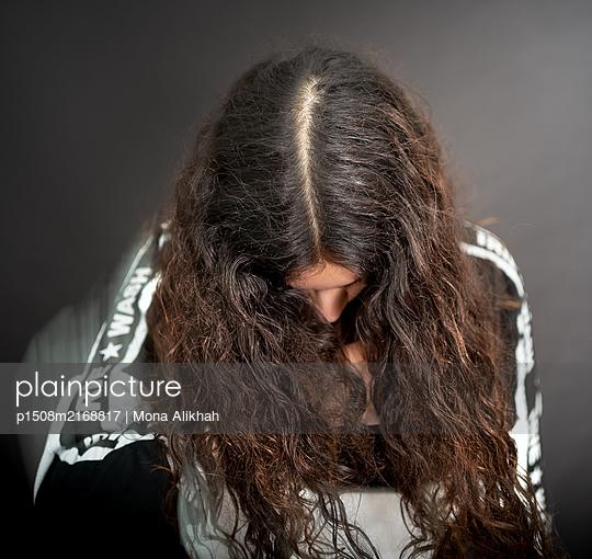 Junge Frau mit langen Haaren blickt nach unten - p1508m2168817 von Mona Alikhah