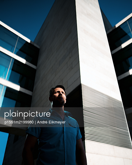 Man stands in front of multistorey building - p1551m2199980 by André Eikmeyer