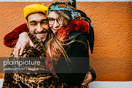 Portrait of smiling mature woman hugging male friend against wall - p426m2279757 by Maskot