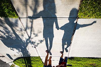Shadow of siblings walking on footpath at yard - p1166m1489098 by Cavan Images