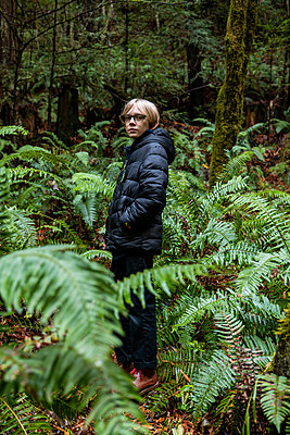 Teenage boy standing in fern grove in Northern California forest - p1166m2165942 by Cavan Images