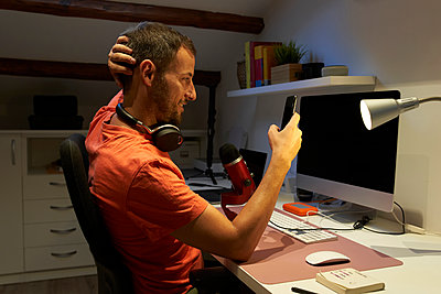 Man with headphone text messaging on smart phone while working from home - p300m2221766 by Veam