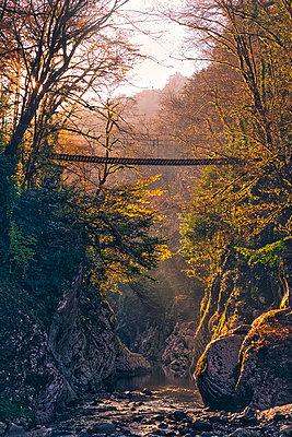 Suspension bridge stretching overKhostaRiver flowing through Devils Gate canyon at sunset - p300m2243773 by Konstantin Trubavin