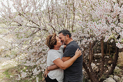 Senior couple embracing each other by tree - p300m2281484 by PICUA ESTUDIO