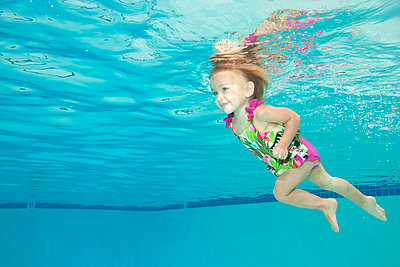 Underwater view of Caucasian girl swimming in pool - p555m1410098 by Ming H2 Wu