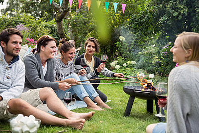 Friends roasting marshmallows at garden party - p788m1165405 by Lisa Krechting