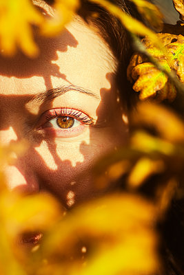 Woman hiding between autumn leaves  - p794m2141730 by Mohamad Itani