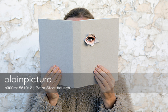 Woman covering face with book, reading poetry, eye looking through cover - p300m1581012 by Petra Stockhausen