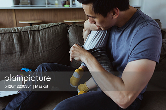 Father checking son's diaper while sitting on sofa in living room - p426m2238934 by Maskot