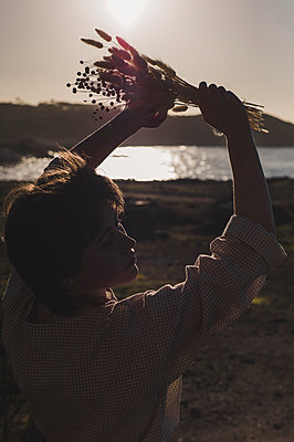 France, Brittany, Sunset, Young woman with bouquet of flowers on the seashore, portrait - p1150m2264240 by Elise Ortiou Campion