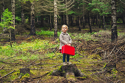 Full length of girl with red briefcase standing on tree stump at forest - p1166m1543850 by Cavan Images