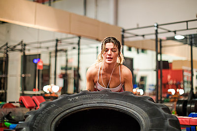 Young attractive woman lifting up a tractor tire - p1166m2084298 by Cavan Images